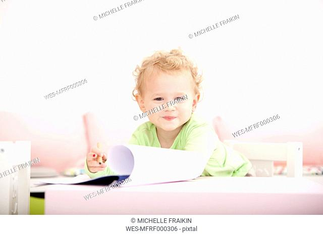 Portrait of little blond girl with coloured pencil