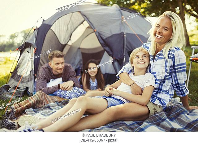Smiling family relaxing outside campsite tent
