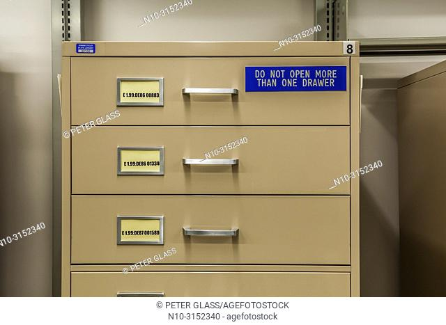 Filing cabinet, with sign reading 'Do Not Open More Than One Drawer' in a library