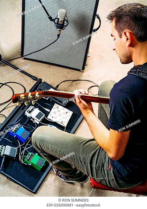 Photo of a man in his late 20's sitting in a rehearsal studio practicing with his electric guitar