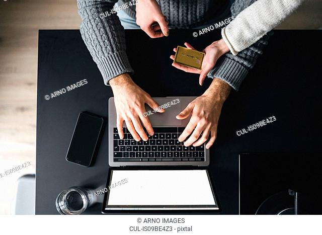 Couple with credit card using laptop, overhead view, cropped