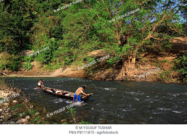tribal people are carring goods by boat on the Sangu river at Tindu Bandarban, Bangladesh