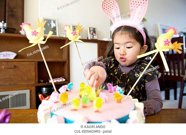 Young girl sitting at table, Easter cake in front of her