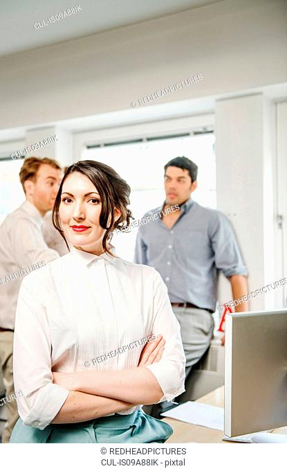 Portrait of female office worker, male colleagues in background