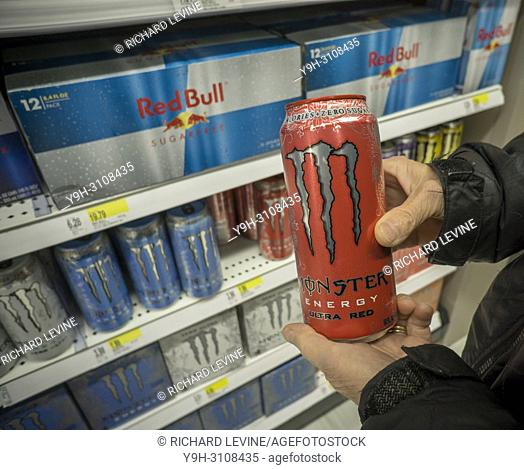 A shopper chooses a can of Monster brand energy drink over its Red Bull competitor in a supermarket in New York on Tuesday, February 27, 2018
