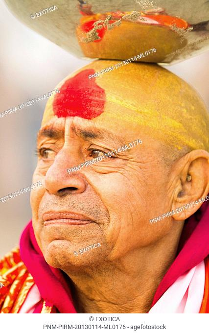 Sadhu balancing a stainless steel pot on his head during Kumbh Mela festival, Allahabad, Uttar Pradesh, India