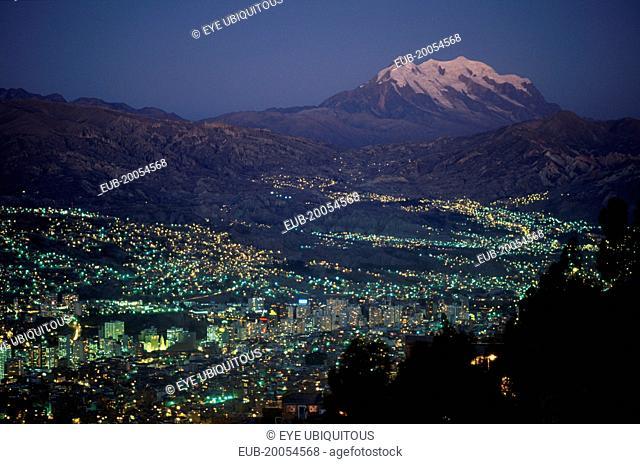Illuminated cityscape and snow capped peak of Mount Illimani at dusk
