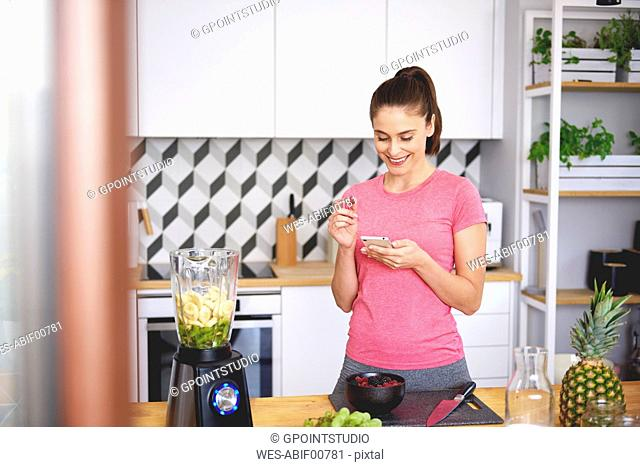 Smiling young woman looking at cell phone in the kitchen