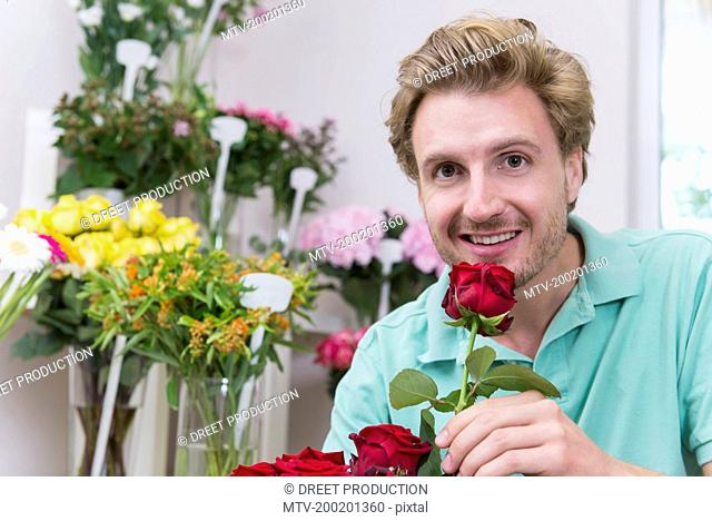 Portrait of mid adult man holding red rose, smiling