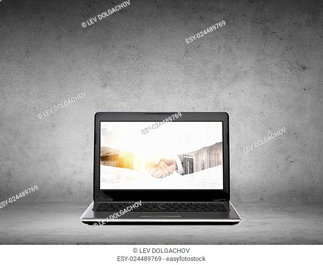 cooperation, partnership, technology and business concept - laptop computer with handshake on screen over gray concrete background with double exposure effect