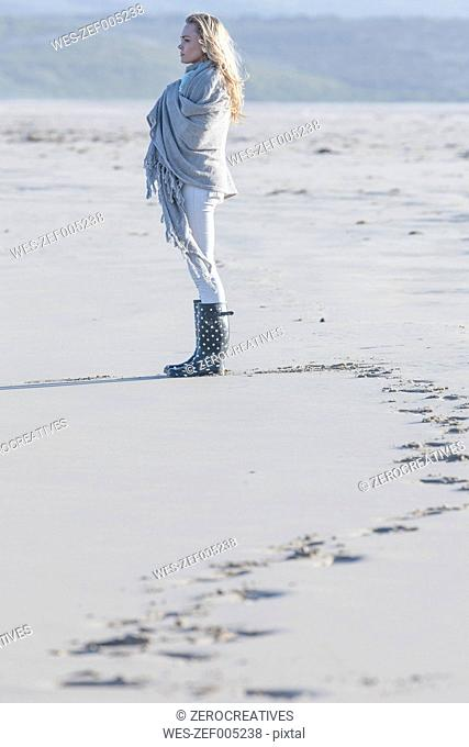 South Africa, Cape Town, young woman standing on the beach looking at distance