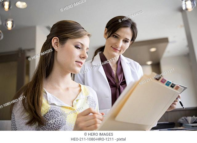 Dentist and receptionist reviewing medical records