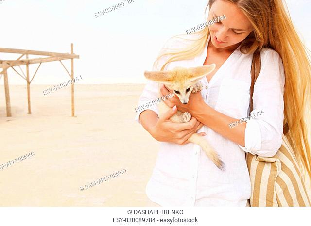 Young woman holding fennec fox in her hands during traveling in Sahara