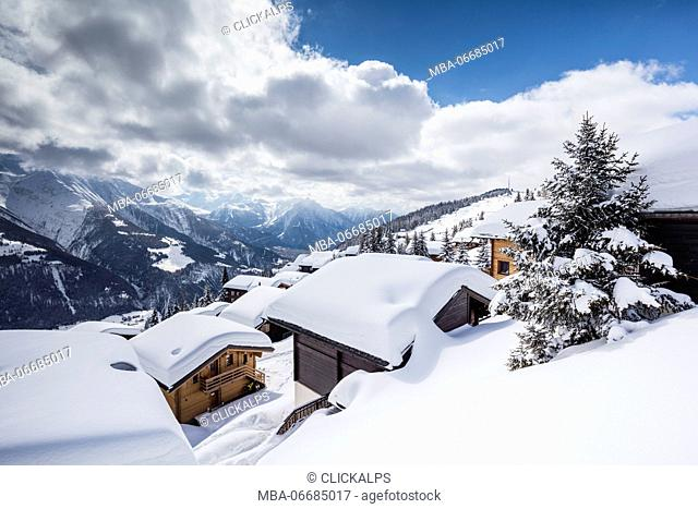 Clouds and blue sky frame the mountain huts covered with snow Bettmeralp district of Raron canton of Valais Switzerland Europe