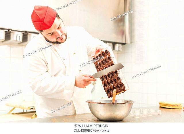 Chef scraping chocolate from chocolate mould