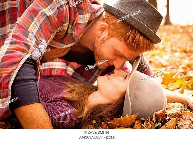 Young couple face to face on autumn forest floor