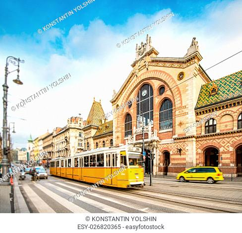 Central Market Hall in Budapest city, Hungary, Europe. Pedestrian crossing and yellow tram in foreground, old building and blue sky in background