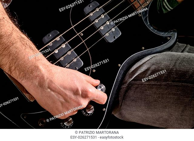 Detail of an electric guitar. Hands moving on the keyboard. Close up. Score and guitar