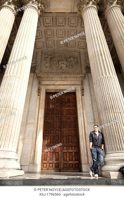 man leaning against one of the columns at the entrance to Saint Pauls Cathedral in London