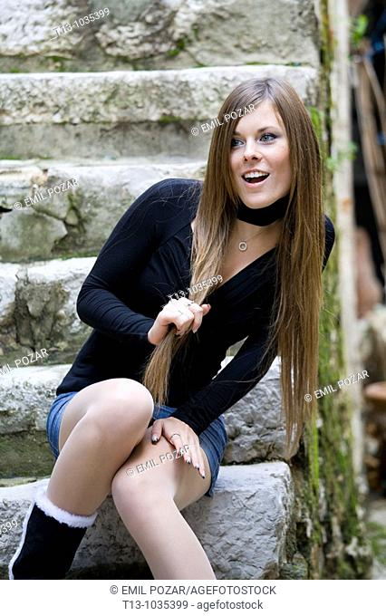 Attractive young woman is sitting on a stone staircase, surprised