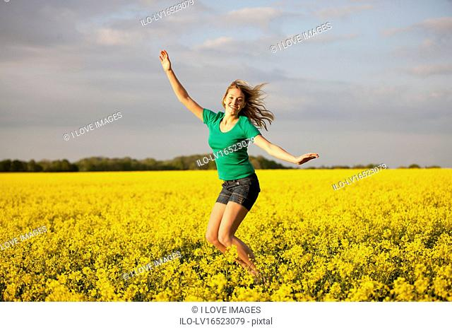 A young woman jumping in a rape seed field