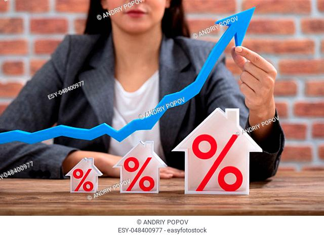 Close-up Of Businesswoman Showing Growth In Real Estate Sitting At Desk Against Brick Wall