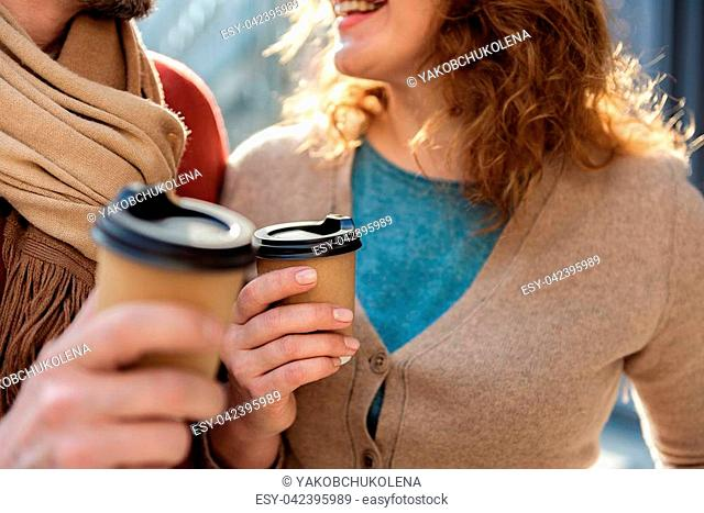 Close up of male and female hands holding cups of coffee. Woman is standing near man and smiling. Focus on beverage