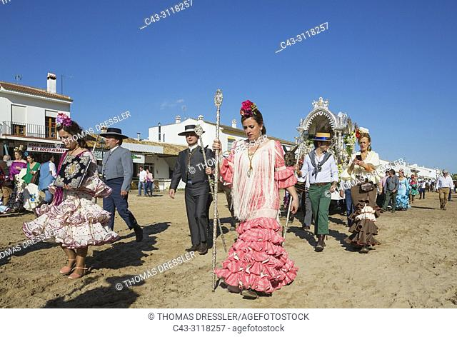 Women wearing beautifully coloured gypsy dresses and dressed up men during the annual Pentecost pilgrimage of El Rocio. Huelva province, Andalusia, Spain
