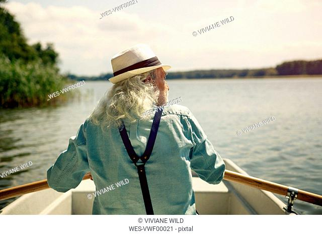 Back view of senior man sitting in rowing boat on a lake wearing suspenders and summer hat