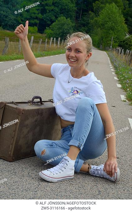 Hitch-hiking young woman, 25 years old, sit on a countryroad in Scania, Sweden; Europe,