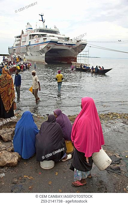 Muslim women with colorful headscarfs waiting for the fishermen turning back from the catch at the daily fish market by the seaside, Stone Town, Unguja Island