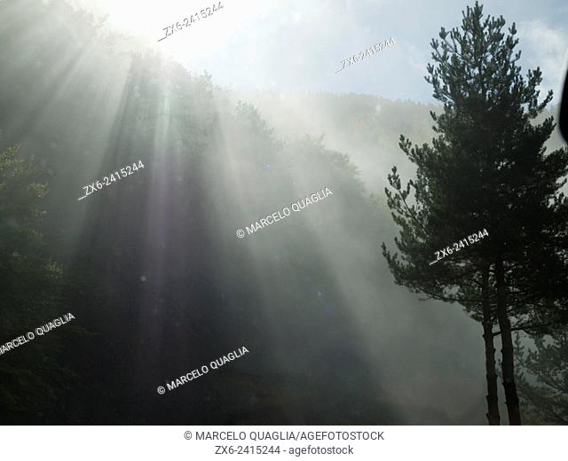 Sun rays through morning mist. Cadí Moixeró Natural Park at Bagà village countryside. Berguedà region, Barcelona province, Catalonia, Spain