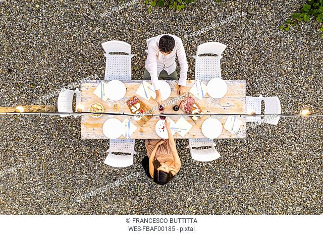 Italy, Tuscany, Siena, top view of young couple dining al fresco clinking red wine glasses