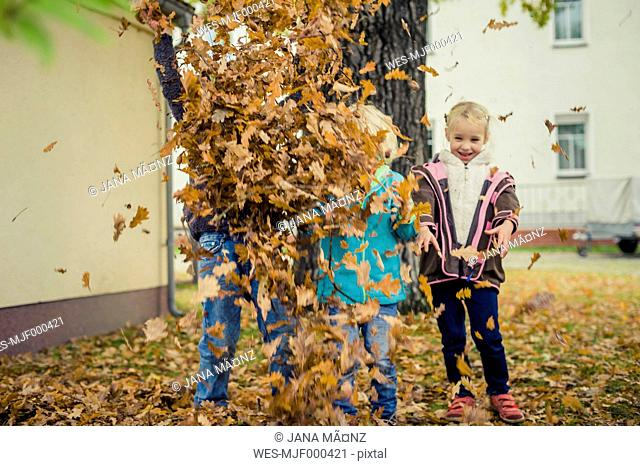 Three children throwing autumn leaves