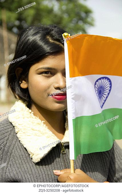 Close-up of young Indian girl holding Indian National flag covering half her face, Pune