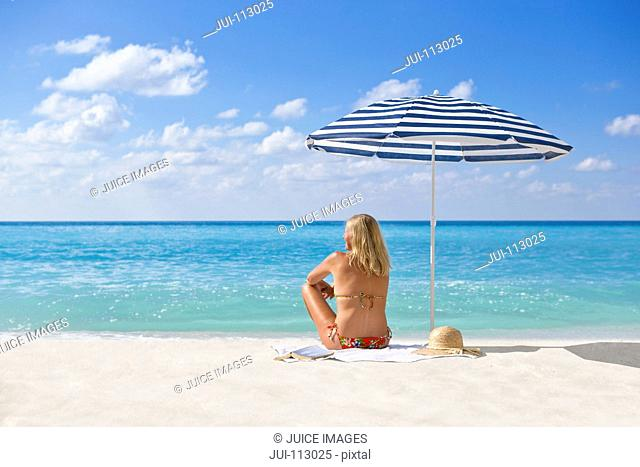 Woman relaxing on sunny beach under striped beach umbrella