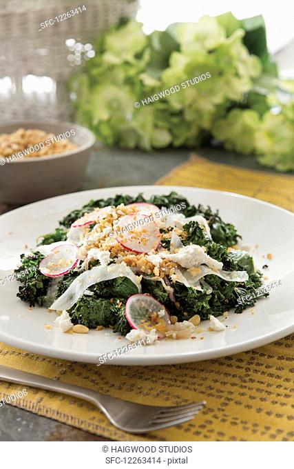 Grilled kale salad with sliced radish and pine nuts garnish