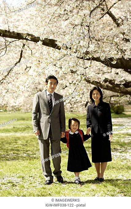 Portrait of a family standing under tree