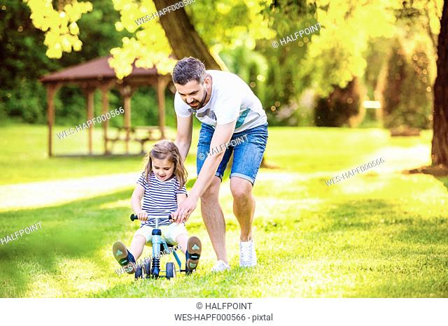 Father and his little daughter with toy car in a park