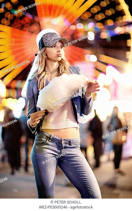 Young woman at fun fair eating candy floss
