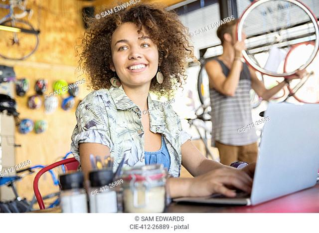 Smiling woman working at laptop in bicycle shop