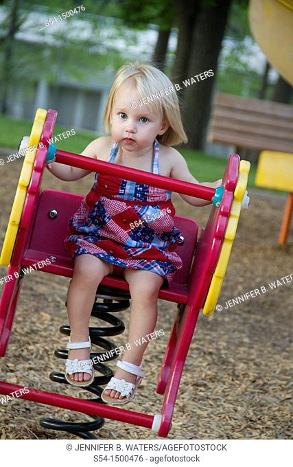 A female caucasian toddler, 1-2 years old, on a toy at the park in Spokane, Washington, USA