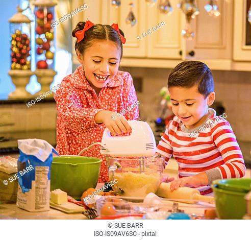 Children in kitchen wearing pyjamas using hand mixer on cookie dough smiling