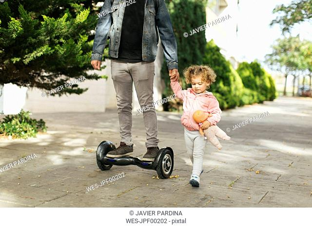 Father on hoverboard hand in hand with his little daughter on pavement
