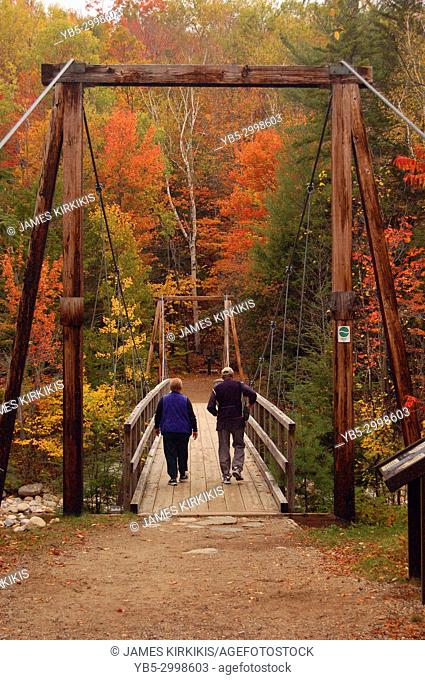Two senior adults cross a pedestrian suspension bridge during fall in the White Mountains