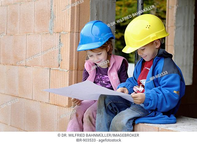 Two little children wearing helmets are planning their rooms at a house construction
