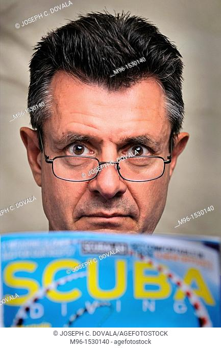 Middle aged man looking at scuba diving magazine close up, Thousand Oaks, California, USA