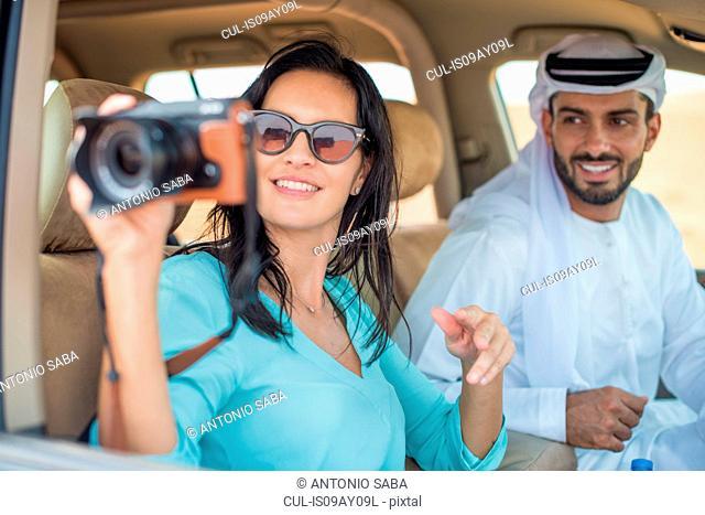Female tourist in off road vehicle in desert taking photographs, Dubai, United Arab Emirates