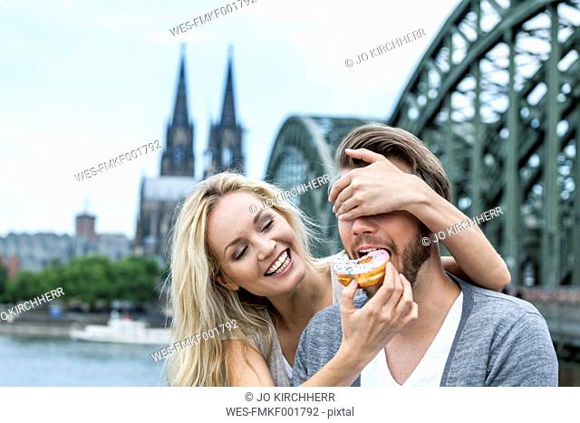 Germany, Cologne, young man tasting a bagel while his girlfriend covering his eyes