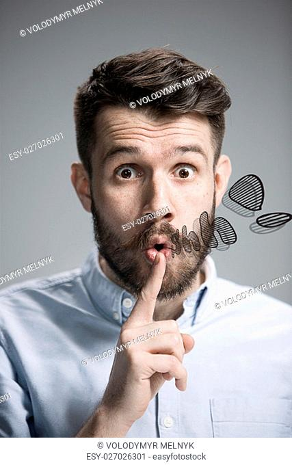 Man wearing a blue shirt is looking wary and saying Shh. Over gray background